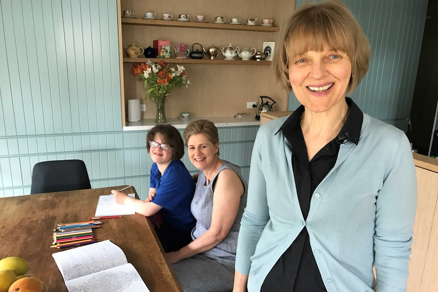 Pia Casalaz in a blue cardigan smiles at the camera with daughter Chiara Casalaz and Kathleen Horan in the background.