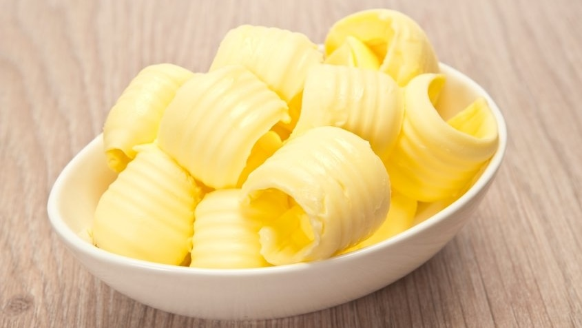 A small bowl filled with curls of butter.
