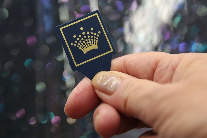 A close-up of a plastic pick with the Crown symbol on it.