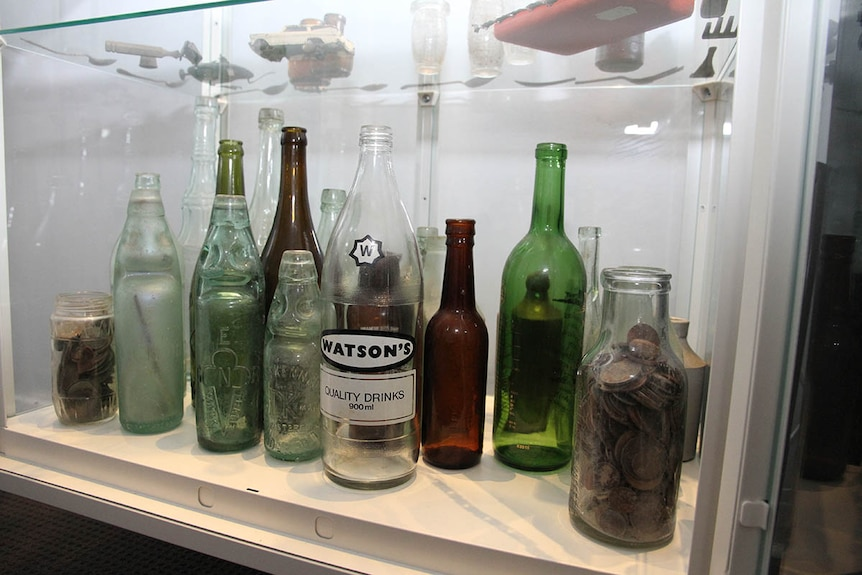 A display cabinet containing antique bottles and coins