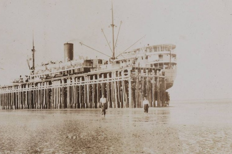A sepia photo of a ship docked at low tide.