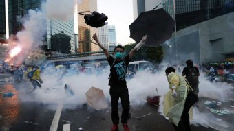 A protester raises his umbrellas in front of tear gas