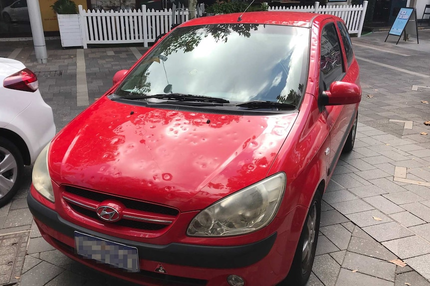 A red car with lots of hail dents in it parked on a road.