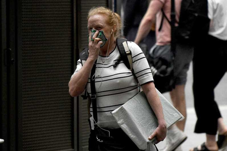 A woman with a face mask on in a Sydney street.