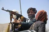 A Taliban terrorist stands in an open-top vehicle holding a gun in Kabul.