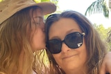 Bo Duincan kisses and hugs her mother Deb Duncan on the side of her face.