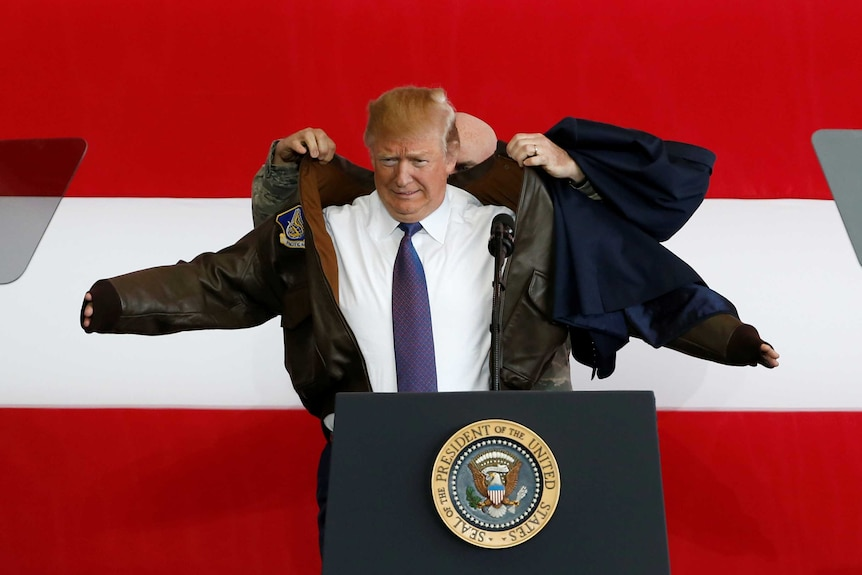 A man helps another man put on a flight jacket in front of a large American flag.
