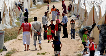 Syrian refugees walk past tents.