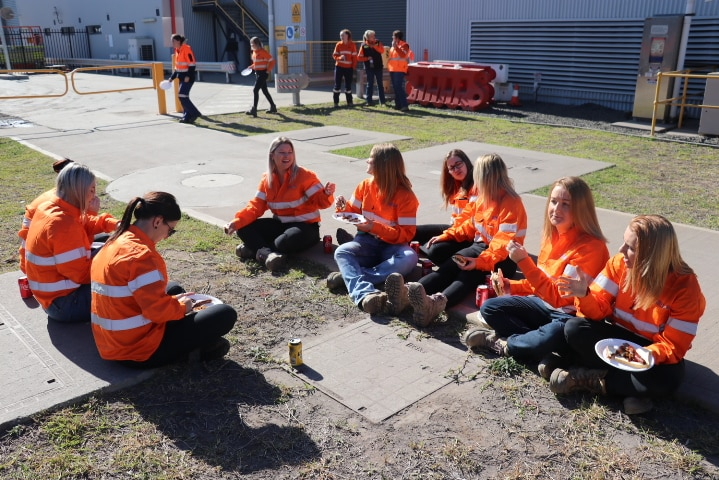 Group of women wearing hi-vis sit together, eating lunch