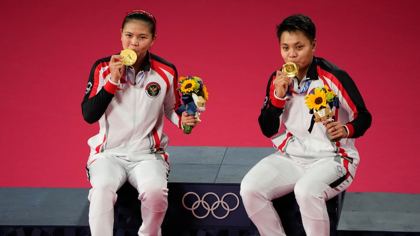 Two women sit smiling with Olympic gold medals