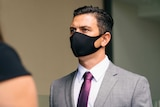 A close up of Nathan wearing a grey suit and purple tie, with a black face mask, walking into court.