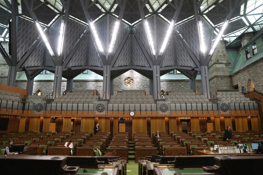 Canada's house of commons, with rows of green and wood benches.