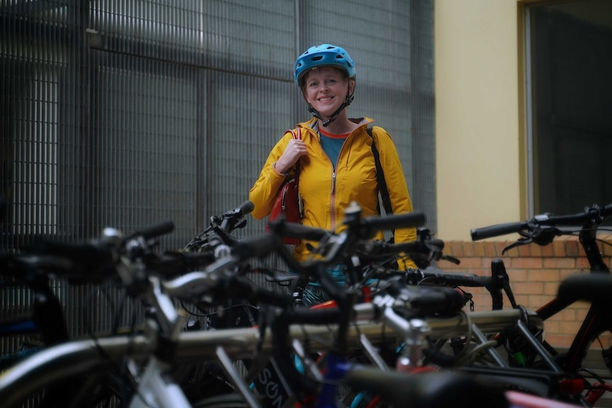 A woman in a yellow jacket and blue cycling helmet stands behind lots of bicyles.