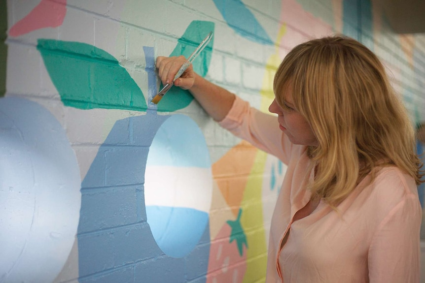 A young woman holds a paint brush while painting a mural on a brick wall.