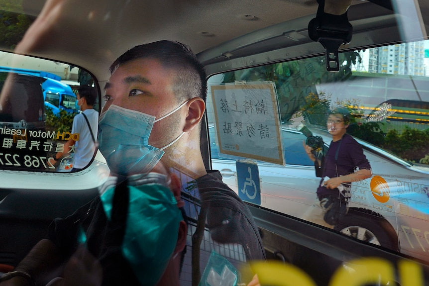 A man wearing a face mask sits in the back of a car