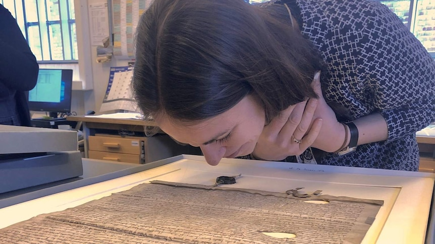Dr Alexy Karenowska bends down to smell the Magna Carta, using her hands to hold her hair back.