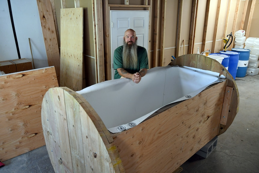 A man with a very long beard and no hair leans over an open coffin like structure