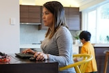 A pregnant woman in a grey dress working on a laptop at a kitchen table with a child in the background.