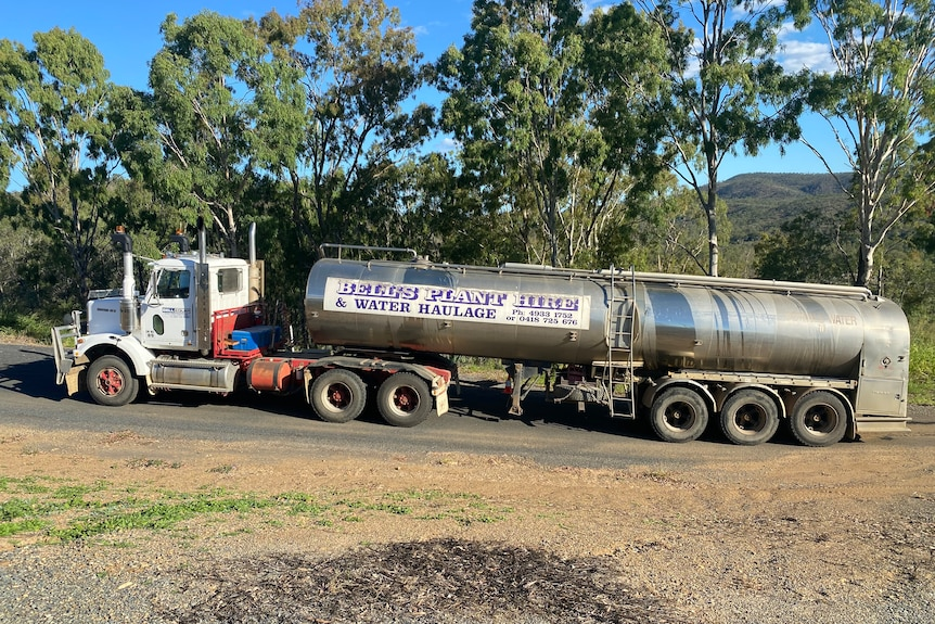 A truck towing a water tanker on a bitumen road with trees behind it