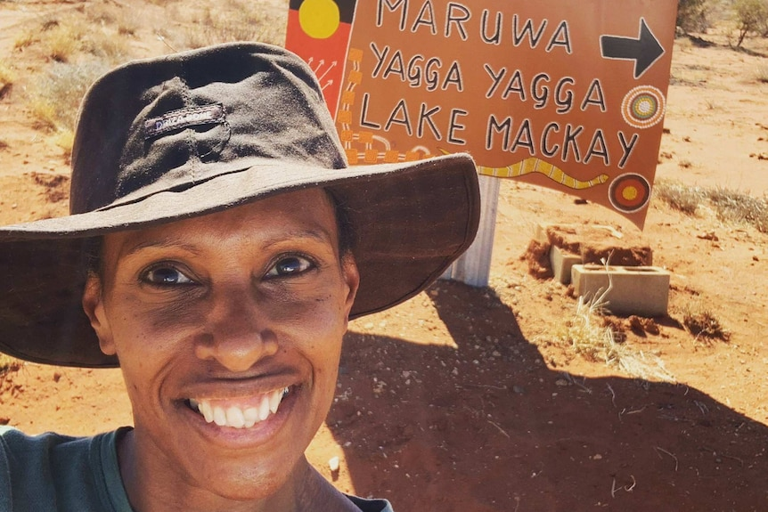 woman in wide brimmed hat in front of sign to communities painted on an old car bonnet.