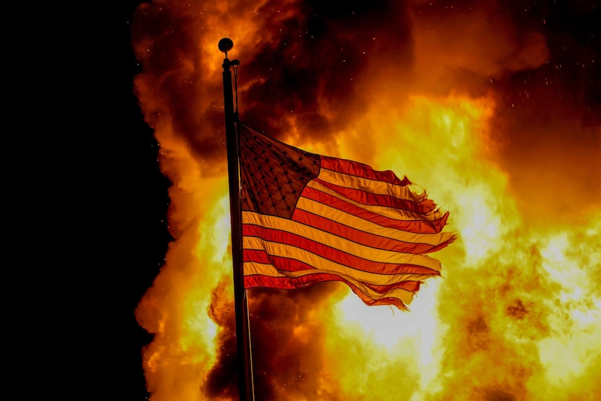 A burning US flag in the night sky