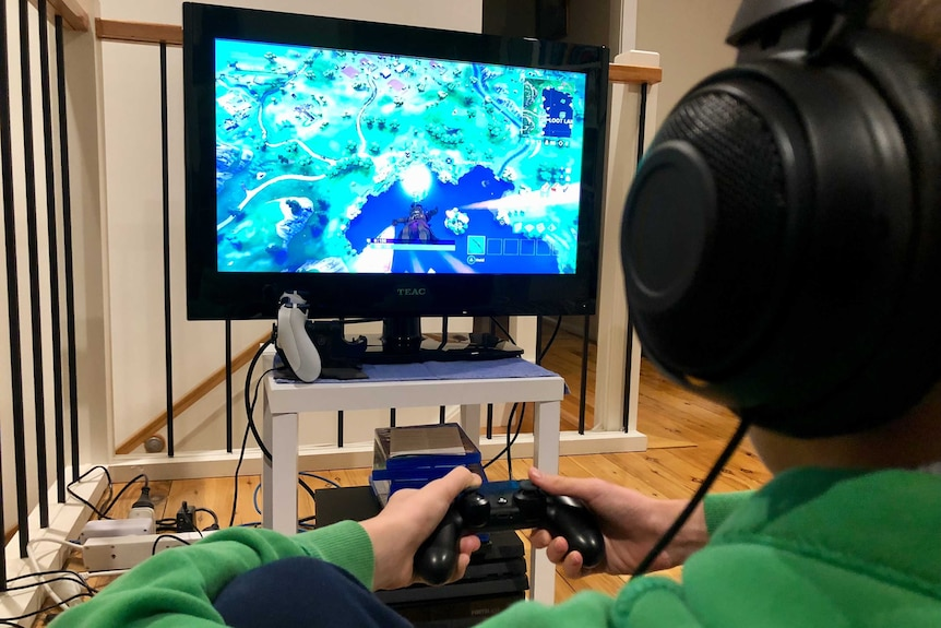 A child sits in front of a television playing a video game.