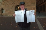 A man standing outside a hotel holding two pieces of paper.