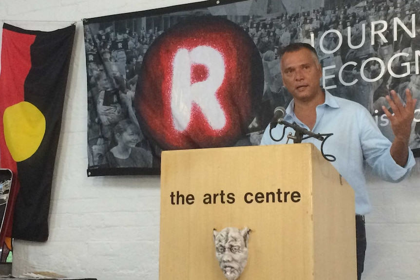 "Stan Grant standing at lectern with Aboriginal flag and the word ""Recognise"" behind him"