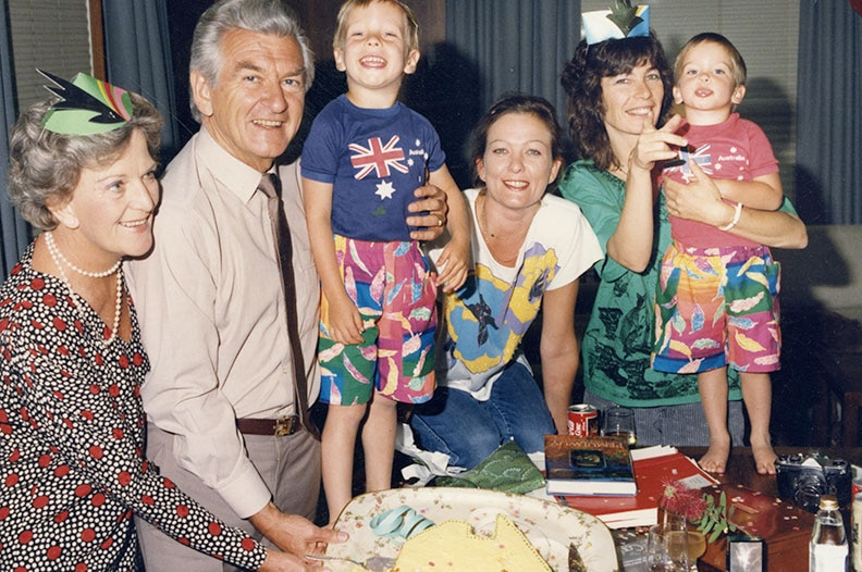 An old film photo of Bob Hawke with his children and grand-children, cutting a cake during a birthday party.
