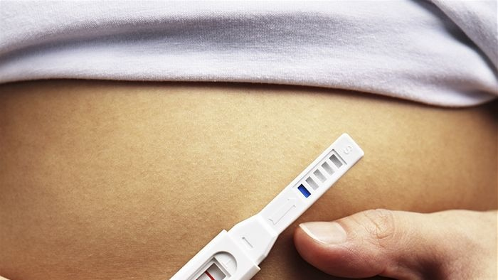 Woman holding a pregnancy test in front of her stomach.