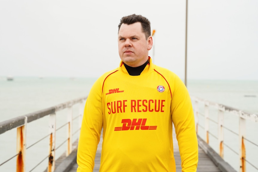 A man in a yellow 'surf rescue' swim shirt stands on an old jetty looking over the water.