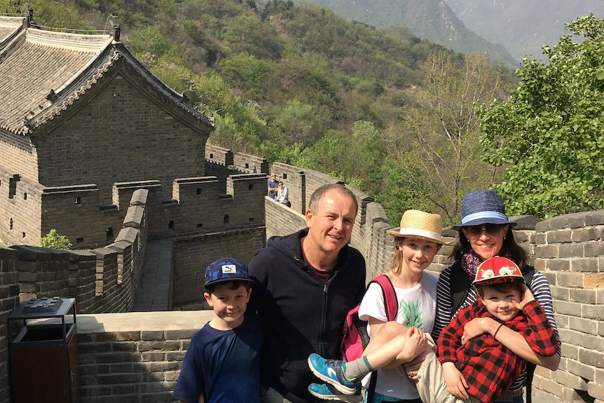 A man with his family stands on a brick wall with mountains in the background