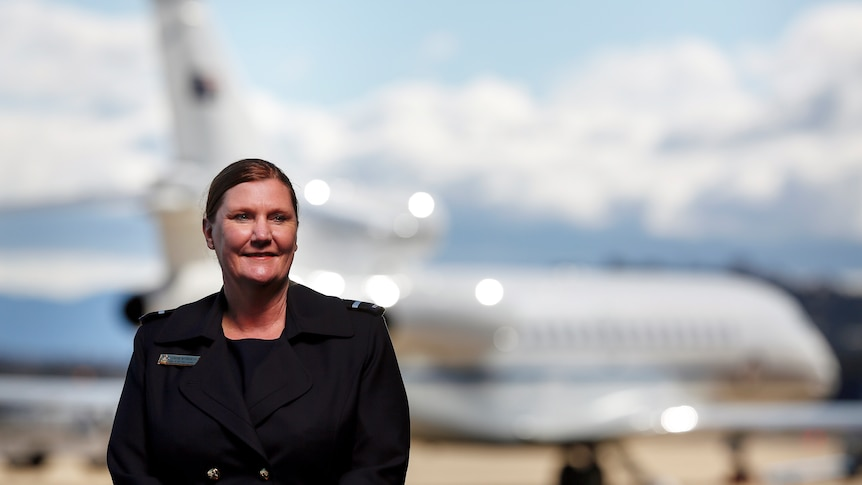 A woman wearing a black blazer with her hair back in a low bun standing in front of an out of focus airplane