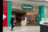 A woman walks in front of Specsavers at West Lakes.