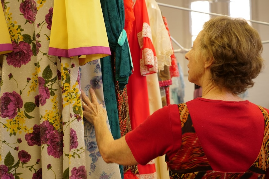 Woman looks at colour dresses hanging.