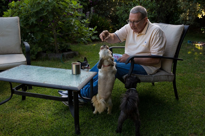 Gary Hughes plays with his dogs in the backyard of his home