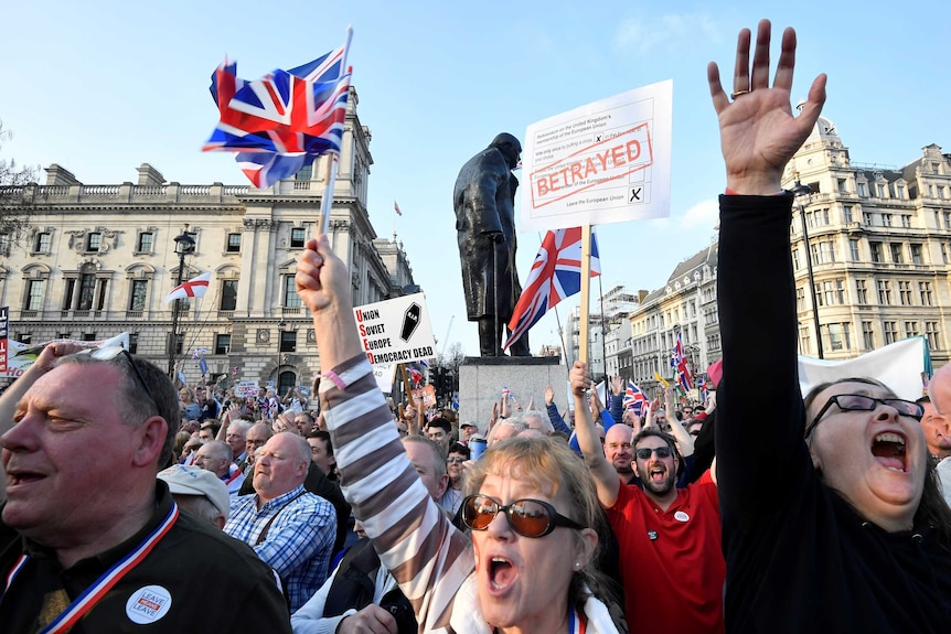 A group of protesters hold their hands in the air in front of a statue of Winston Churchill