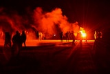 Youths stand in a field during clashes as police tried to break up an unauthorized rave party