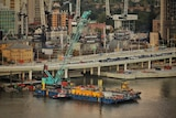Construction site of Queen's Wharf project in Brisbane CBD, with lots of building cranes and construction barge on river.