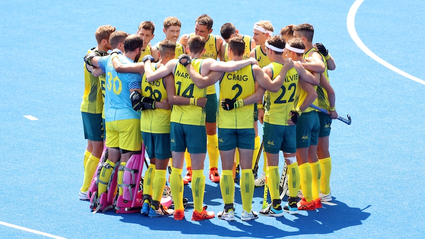 The Australian men's hockey team stand together in a huddle on the field