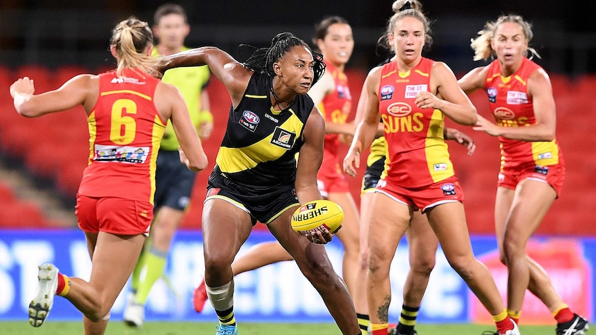 Richmond Tigers AFLW player Sabrina Frederick looks to handpass while surrounded by Gold Coast Suns.