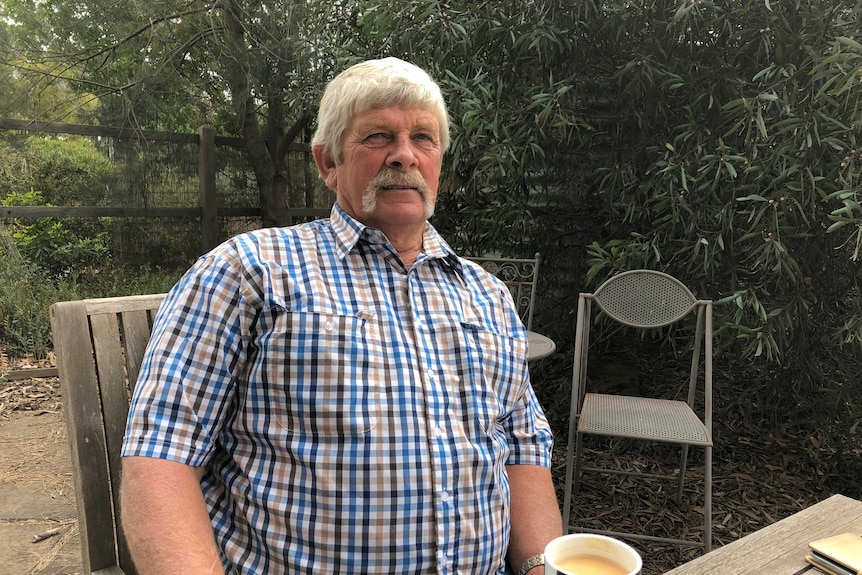 A man in a blue-checked shirt with grey hair and beard sits in a garden