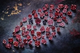 A group of vivid pink, red and violet stones against blue backdrop