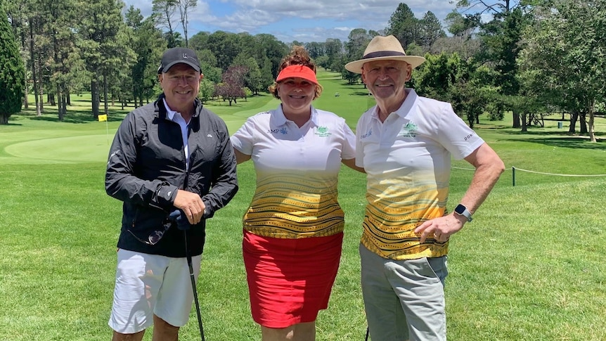 Meryl Swanson stands between Joel Fitzgibbon and Alex Gallacher on a golf course