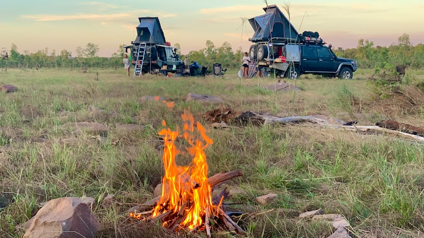 A campfire burns close to where two four-wheel-drive campers are parked