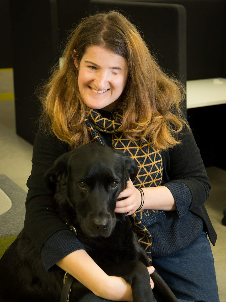 Writer Ellen Fraser-Barbour pats her guide dog, Inka