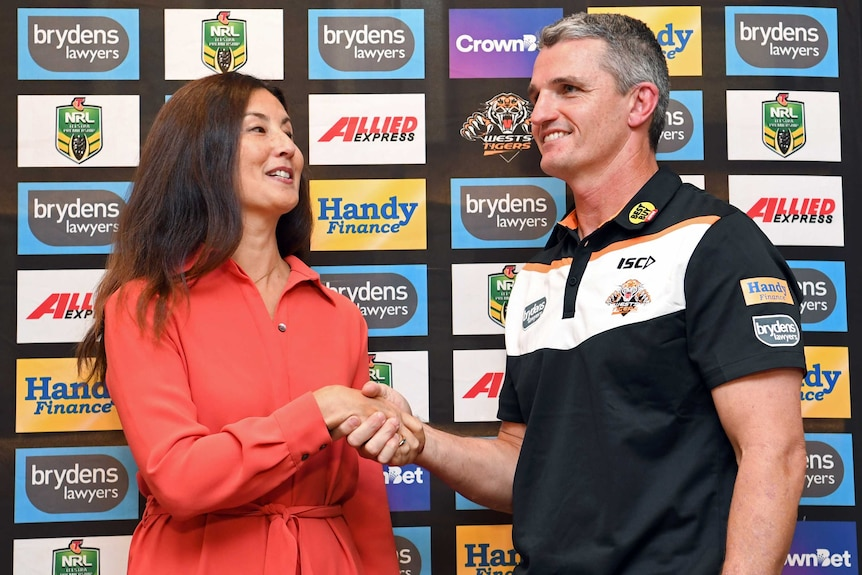 Marino Go and Ivan Cleary smile while shaking hands in front of an advertising board.