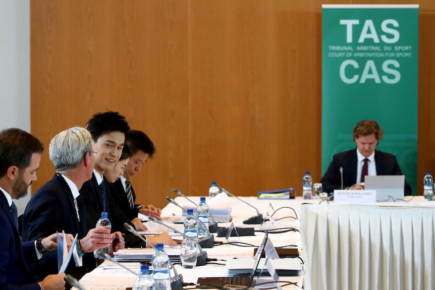 Sun Yang smiling and talking to a man in a suit while seated a the Court of Arbitration for Sport.