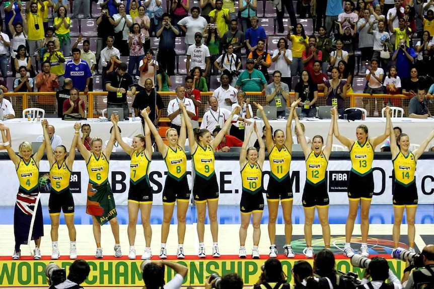 The Australian Opals basketball team stand on the podium raising their hands after winning the FIBA world championships in 2006.