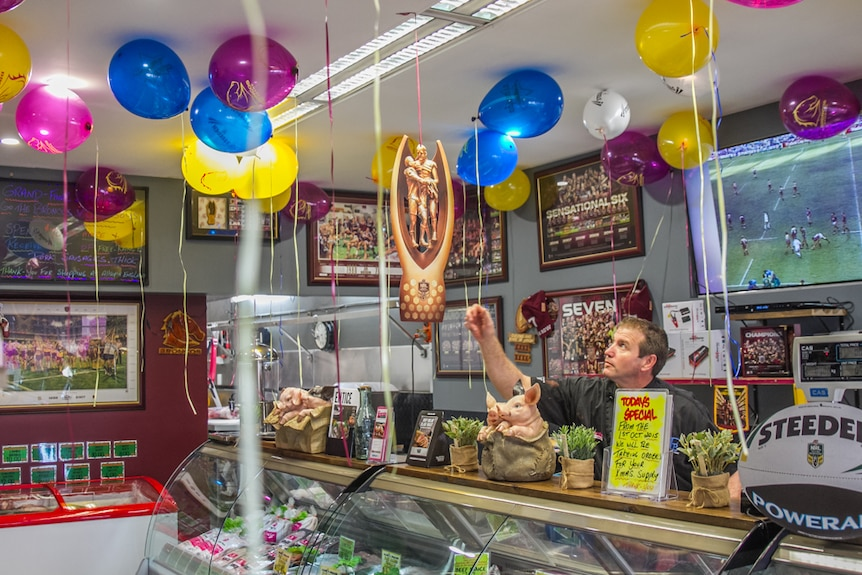 Owner Matt Roberts puts up decorations in the butcher shop ahead of the grand final.